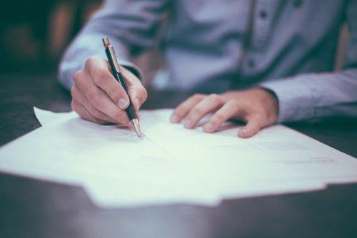 Jemand unterschreibt einen Vertrag