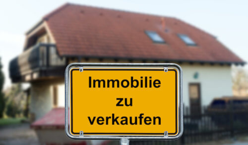 """Haus mit einem """"zu verkaufen"""" Schild im Vordergrund"""