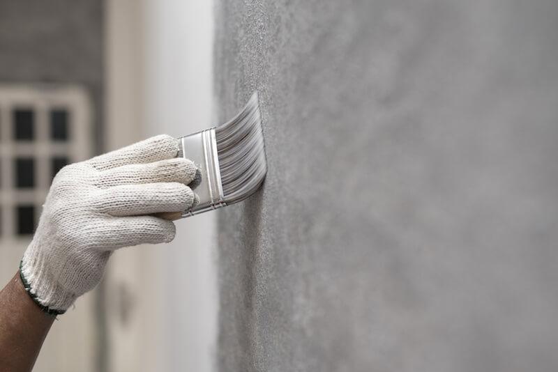 Jemand streicht mit grauer Farbe eine Wohnungswand