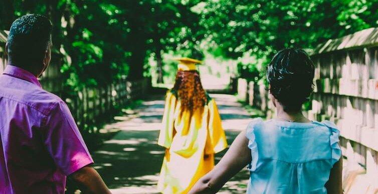 Eltern und ihre Tochter, die ihren Uniabschluss entgegen nimmt