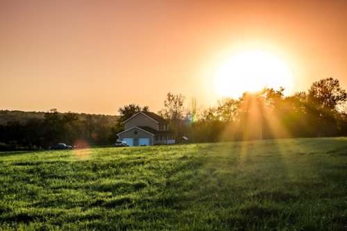 Haus auf dem Feld bei Sonnenuntergang
