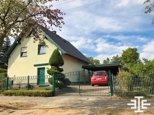einfamilienhaus grundstueck zaun rotes auto