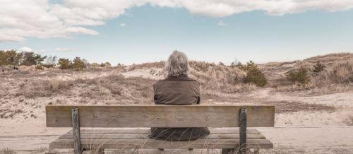 Frau auf einer Bank in schöner Landschaft