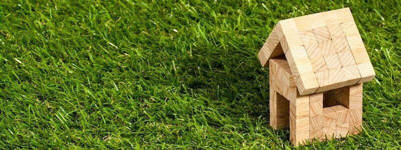 Kleines Spielzeug Holzhaus auf Rasen Grundstück Immobilie verkaufen