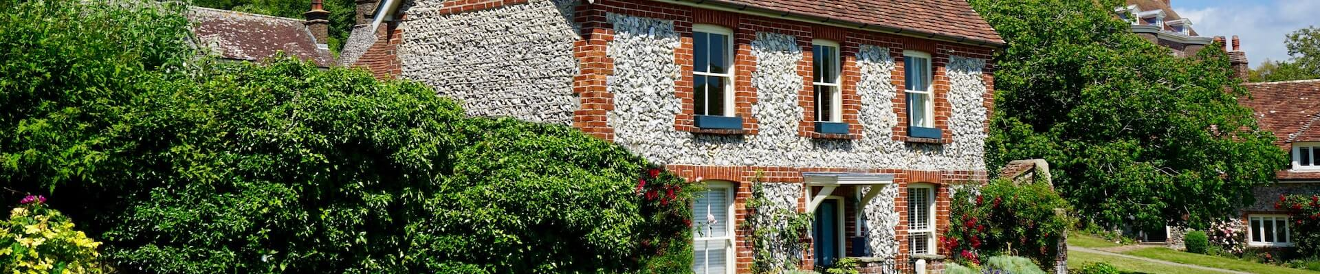 Hausfassade auf Backstein mit Rosengarten davor