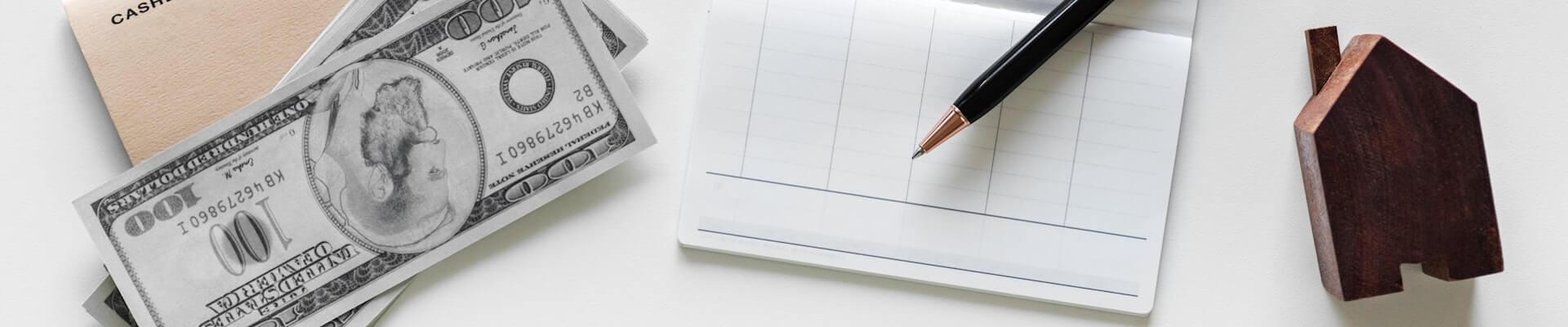 Schreibtisch mit Kugelschreiber, Papier und kleinem Holzhaus